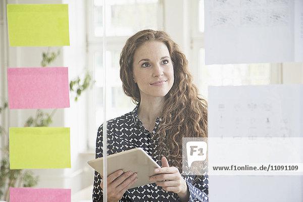 Frau im Büro schaut auf Papiere an der Glasscheibe