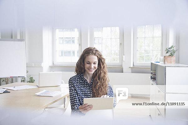 Frau mit Tablette im Sitzungssaal