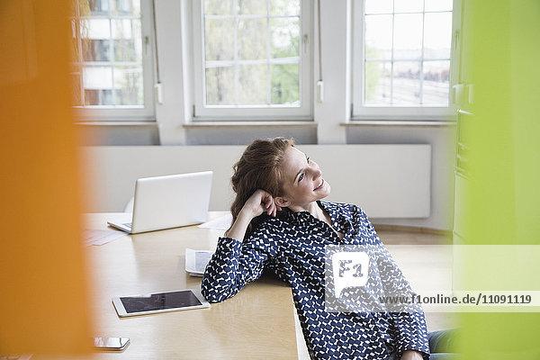 Lächelnde Frau im Büro auf den Tisch gelehnt