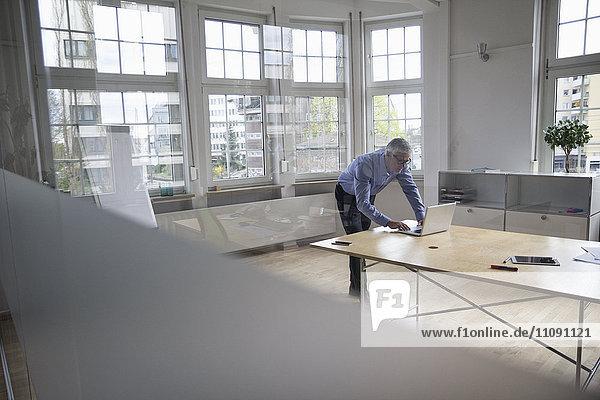 Ein reifer Geschäftsmann  der seinen Laptop auf dem Boardroom-Tisch benutzt.