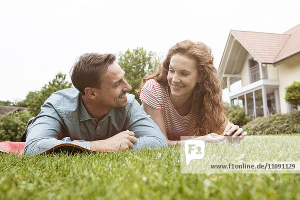 Smiling couple lying on lawn in garden