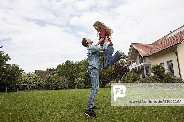Glücklicher Mann hebt Frau im Garten hoch