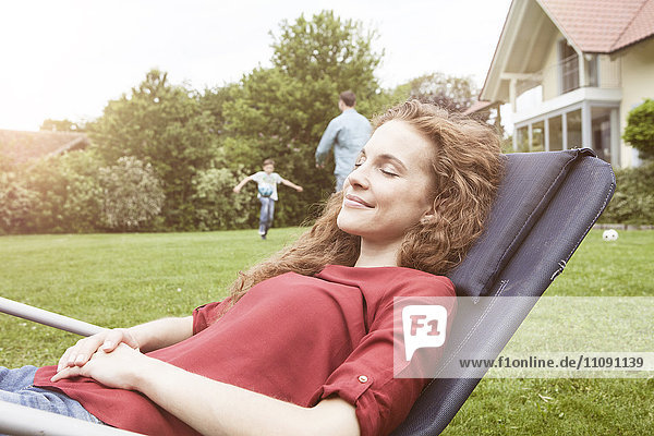 Woman relaxing in deckchair in garden with family in background