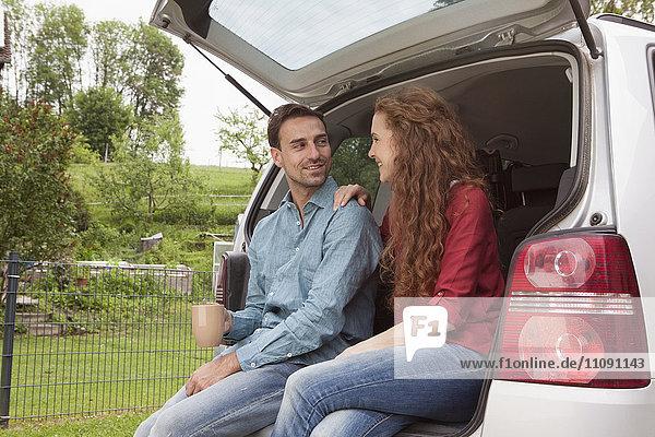 Lächelndes Paar im Kofferraum sitzend