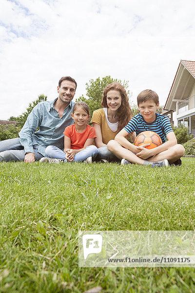 Portrait of smiling family sitting in garden