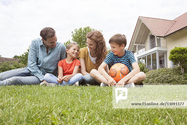 Smiling family sitting in garden with football