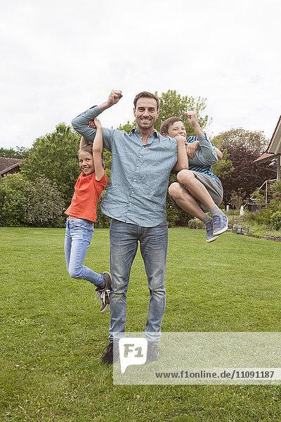 Porträt des glücklichen Vaters mit seinen beiden Kindern im Garten