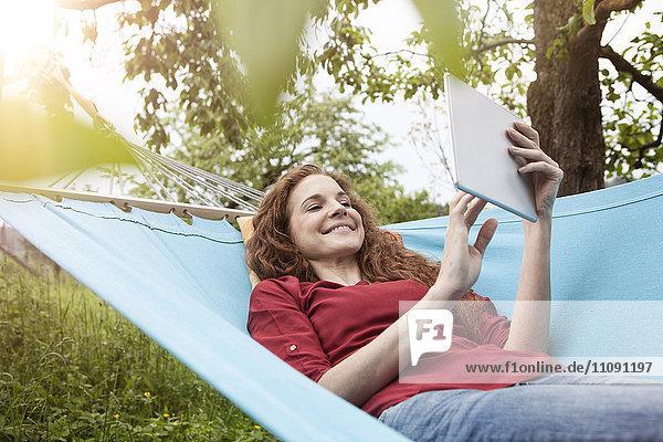 Lächelnde Frau in der Hängematte mit Tablette