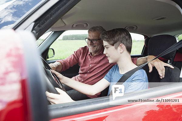 Vater unterrichtet den Sohn beim Autofahren