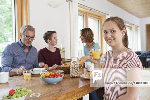 Porträt eines Mädchens beim Frühstück mit seiner Familie zu Hause