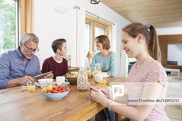 Familie mit tragbaren Geräten während des Frühstücks zu Hause