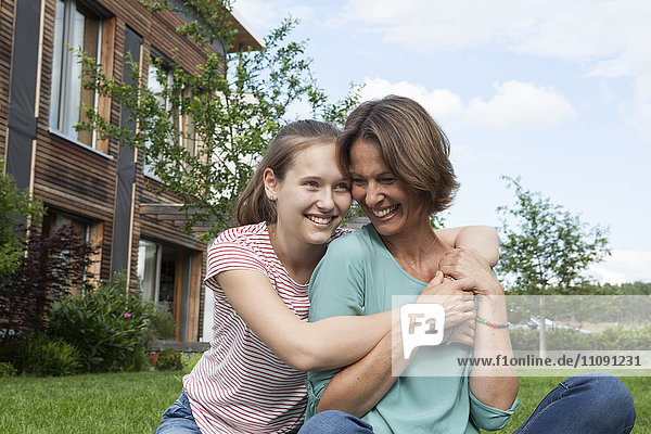 Happy mother and daughter sitting in garden