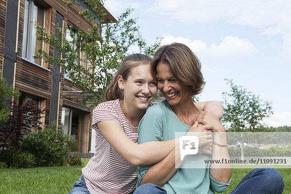Glückliche Mutter und Tochter im Garten sitzend