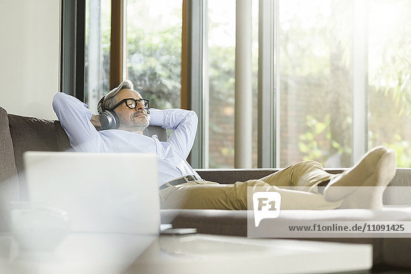 Mann entspannt auf der Couch Musik hören mit Kopfhörer