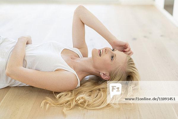 Lächelnde blonde Frau auf Holzboden liegend