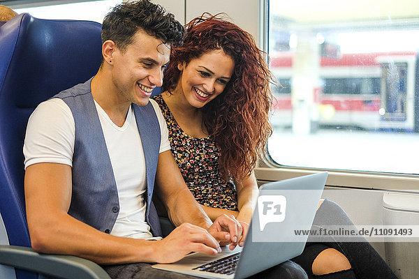 Lächelndes junges Paar im Zug mit Laptop