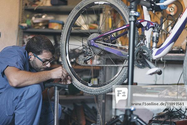 Mechanic in repair shop repairing bicycle