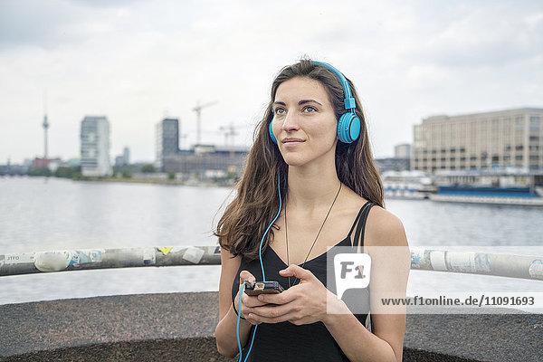 Deutschland  Berlin  entspannte Frau beim Musikhören mit Kopfhörer