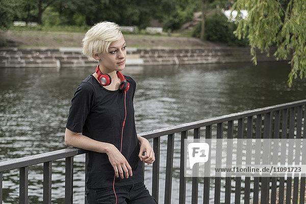 Junge Frau mit Kopfhörern  die sich vor dem Wasser auf das Geländer lehnen.