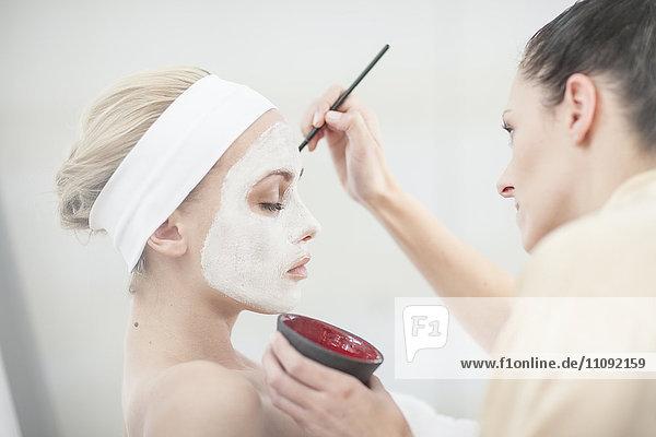Junge Frau im Spa mit Gesichtsmaske