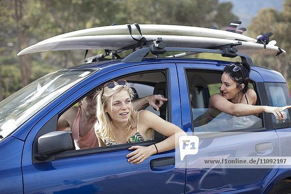 Freunde omn eine Fahrt im Auto mit Surfbrettern auf dem Dach