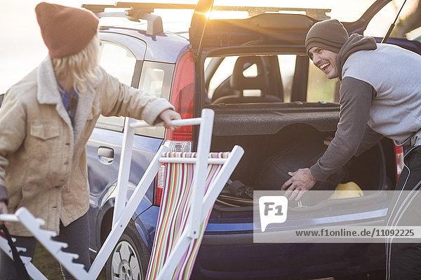 Glückliches Paar  das bei Sonnenuntergang seine Sachen im Auto packt.
