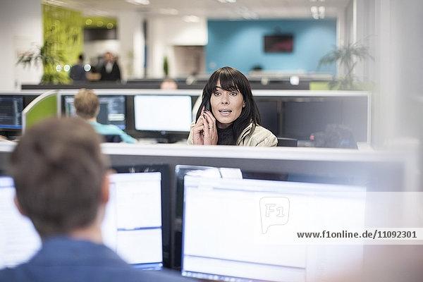 Frau am Telefon im Büro mit Blick auf Kollegen