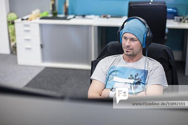 Junger Mann mit Kopfhörer bei der Arbeit am Computer im Büro