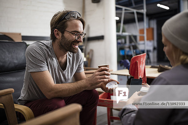 Mann und Frau beim Kaffeetrinken in der Werkstatt