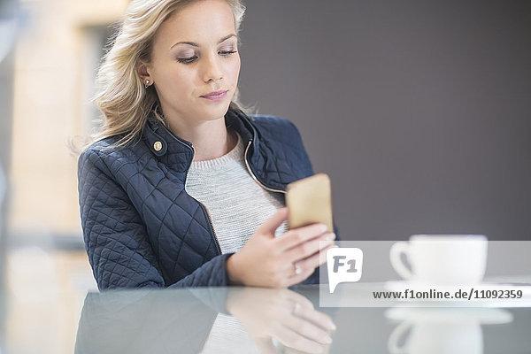Blonde Frau in der Kantine beim Lesen von Nachrichten auf dem Smartphone