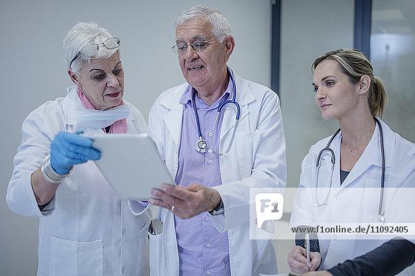 Drei Ärzte mit digitalem Tablett im Gespräch