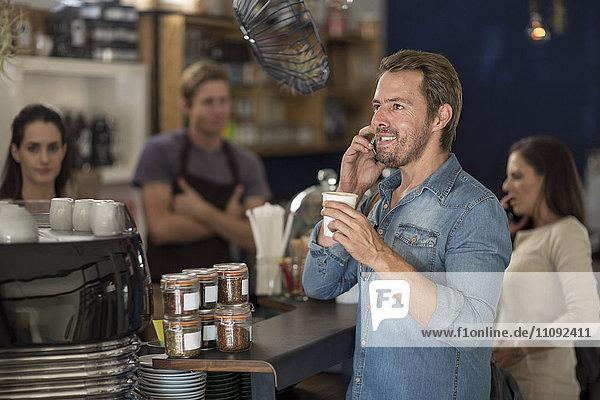 Mann am Telefon in einem Cafe