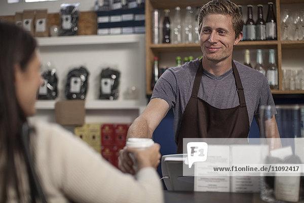 Mann im Café bei der Übergabe der Einweg-Kaffeetasse