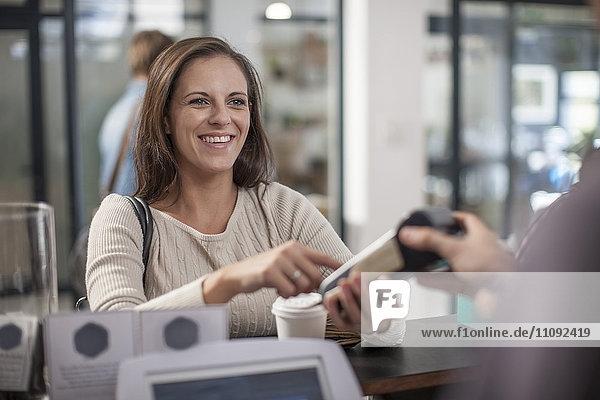 Kunde zahlt bargeldlos für Kaffee zum Mitnehmen