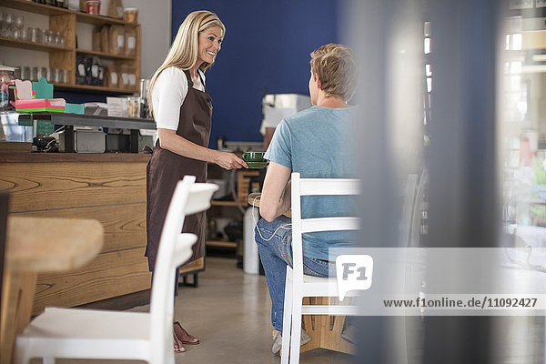 Waitress serving coffee to man in a cafe
