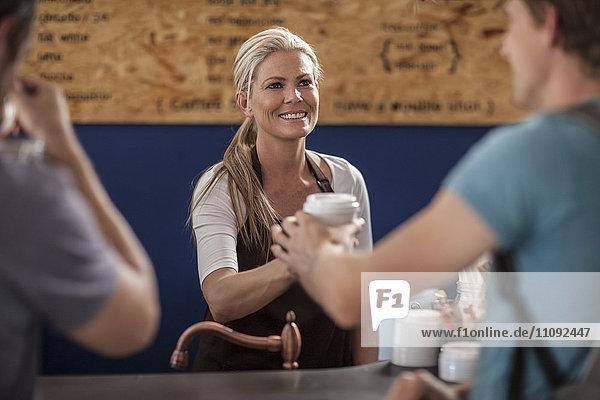 Frau im Café bei der Übergabe der Einweg-Kaffeetasse