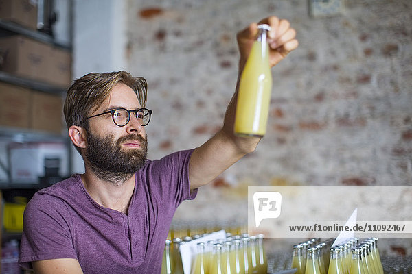 Mann kontrolliert den Vorrat an Saftflaschen im Lager