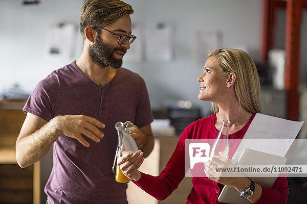 Mann und Frau diskutieren im Lagerhaus mit Saftflaschen