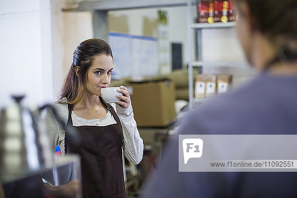 Woman drinking coffee from cup looking at man