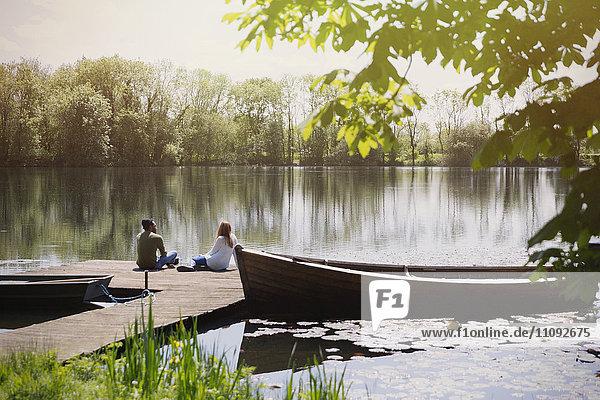 Pärchen entspannen sich am sonnigen Seeufer in der Nähe des Kanus