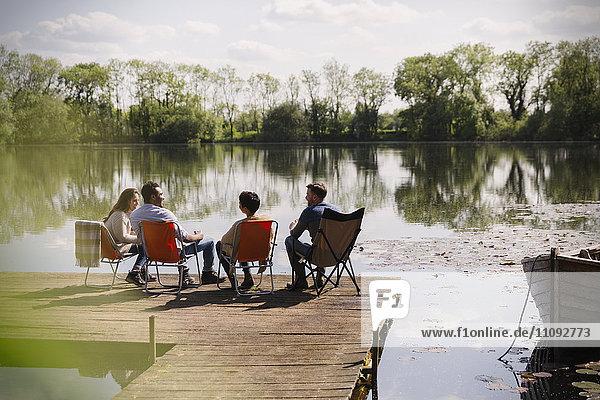 Freunde unterhalten sich am sonnigen Hafen am Seeufer.
