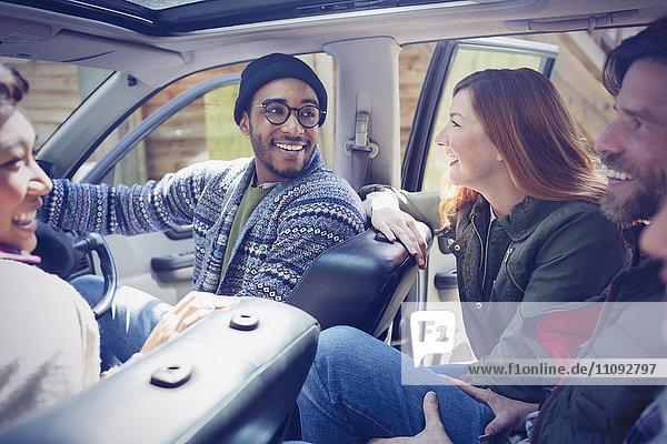 Lächelnde Freunde beim Reden und Fahren im Auto