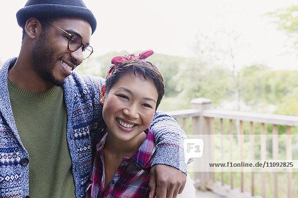 Lächelndes Paar  das sich an Deck umarmt.