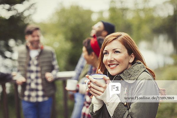 Lächelnde Frau trinkt Kaffee auf dem Balkon