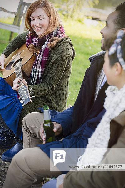 Frau spielt Gitarre mit Freunden beim Biertrinken