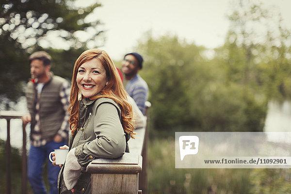Portrait lächelnde Frau beim Kaffeetrinken mit Freunden auf dem Balkon