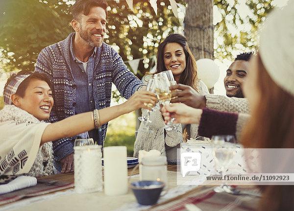 Freunde toasten Champagnergläser am Geburtstagsparty-Tisch