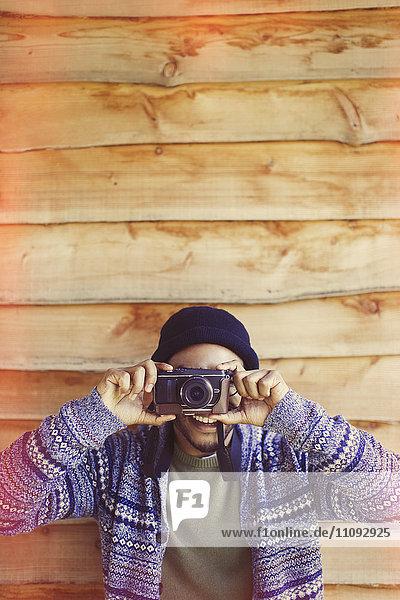 Portrait Verspielter Mann mit Kamera außerhalb der Kabine