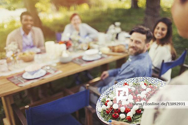 Frau serviert Caprese Salat Vorspeise für Freunde am Terrassentisch