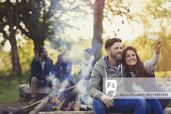 Lächelndes Paar nimmt Selfie mit Fotohandy am Lagerfeuer mit.